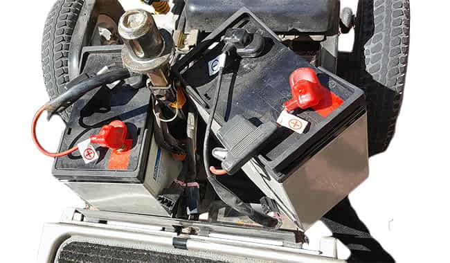 Scooter de mobilité électrique avec le capot ouvert, un câble principal débranché et une batterie AGM 45 AH partiellement enlevée