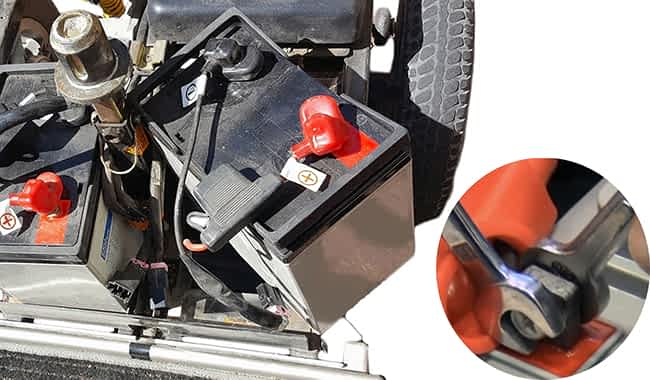 Batterie AGM 55 Ah avec le faisceau de câbles débranché et deux clefs plates qui desserrent le boulon du pôle de batterie d'un scooter électrique senior