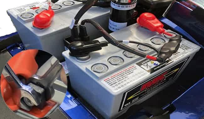 Batterie GEL 51 Ah de MK Battery d'un scooter handicapé électrique avec le faisceau de câbles déconnecté et deux clefs plates qui dévissent un boulon sur la borne de la batterie