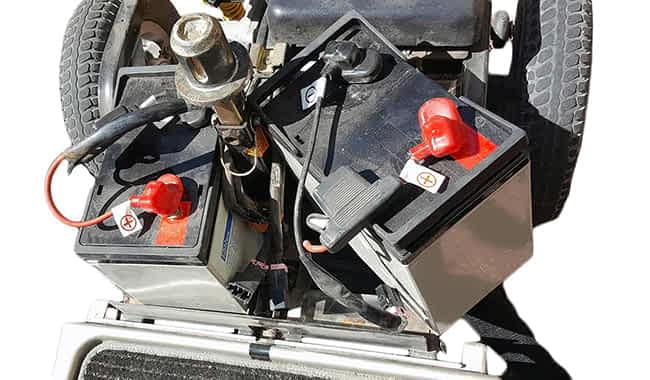 Scooter PMR avec le capot ouvert et une batterie GEL 88 AH partiellement enlevée pour son démontage