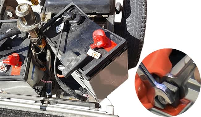 Batterie GEL 55 Ah du scooter de mobilité réduite senior avec le faisceau de câbles déconnecté et deux clefs à fourches à dévisser la boulonnerie du borne de la batterie