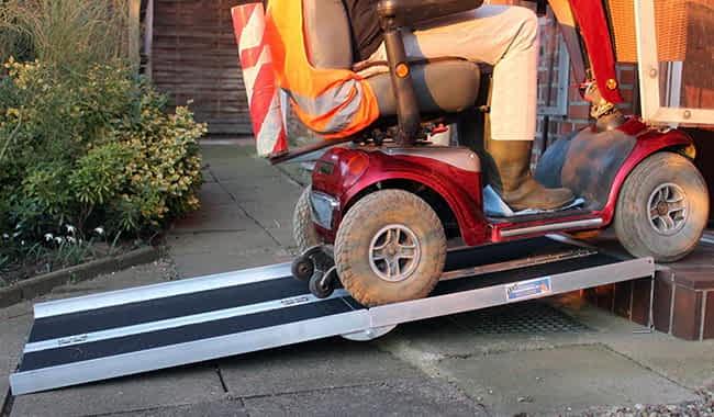 Monsieur sur scooter électrique qui roule sur la rampe d'accès ouverte