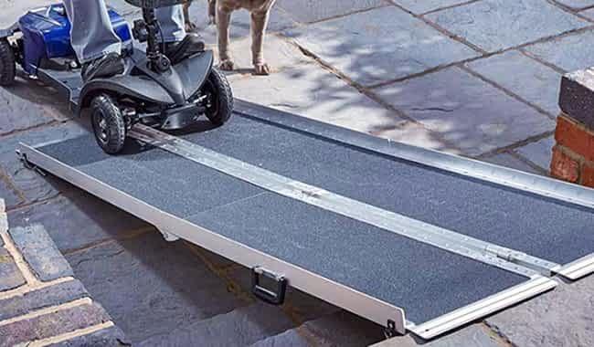 Scooter pour senior et personne handicapée sur la rampe pliable en valise de Kingmobilité