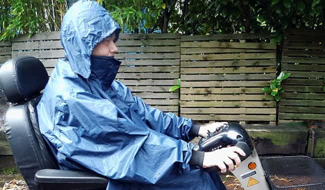 Homme avec poncho avec manches qui porte un capuchon sur scooter PMR pour senior