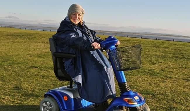 Femme avec poncho de kingmobilité sur un scooter de mobilité électrique