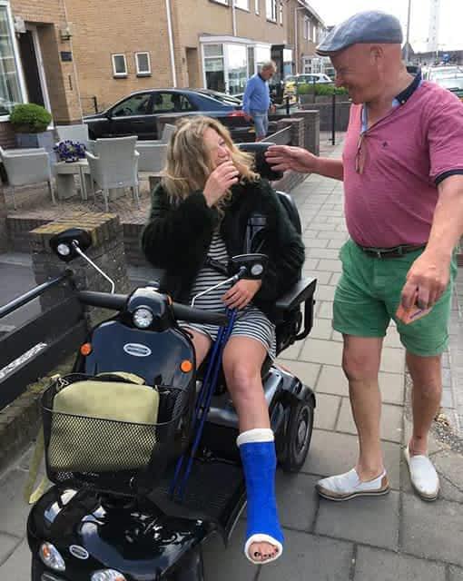 Une dame dans un scooter de mobilité réduite pour personne senior et handicapée entraine de parler avec un monsieur