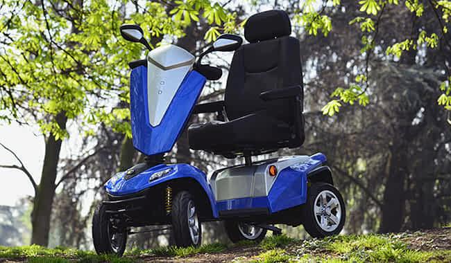 Scooter électrique handicapé Kymco Maxer en bleu en forêt